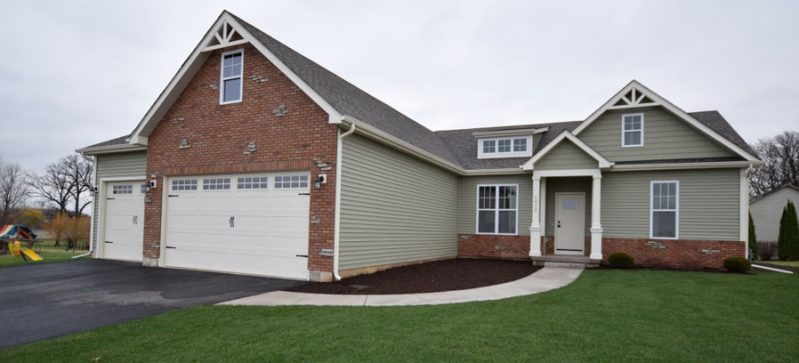 Front exterior of ranch home with brick garage and lighter siding.