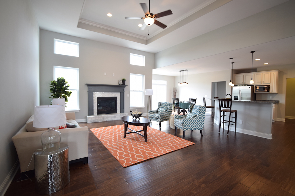 Great room with carpet, couch, chairs and fireplace