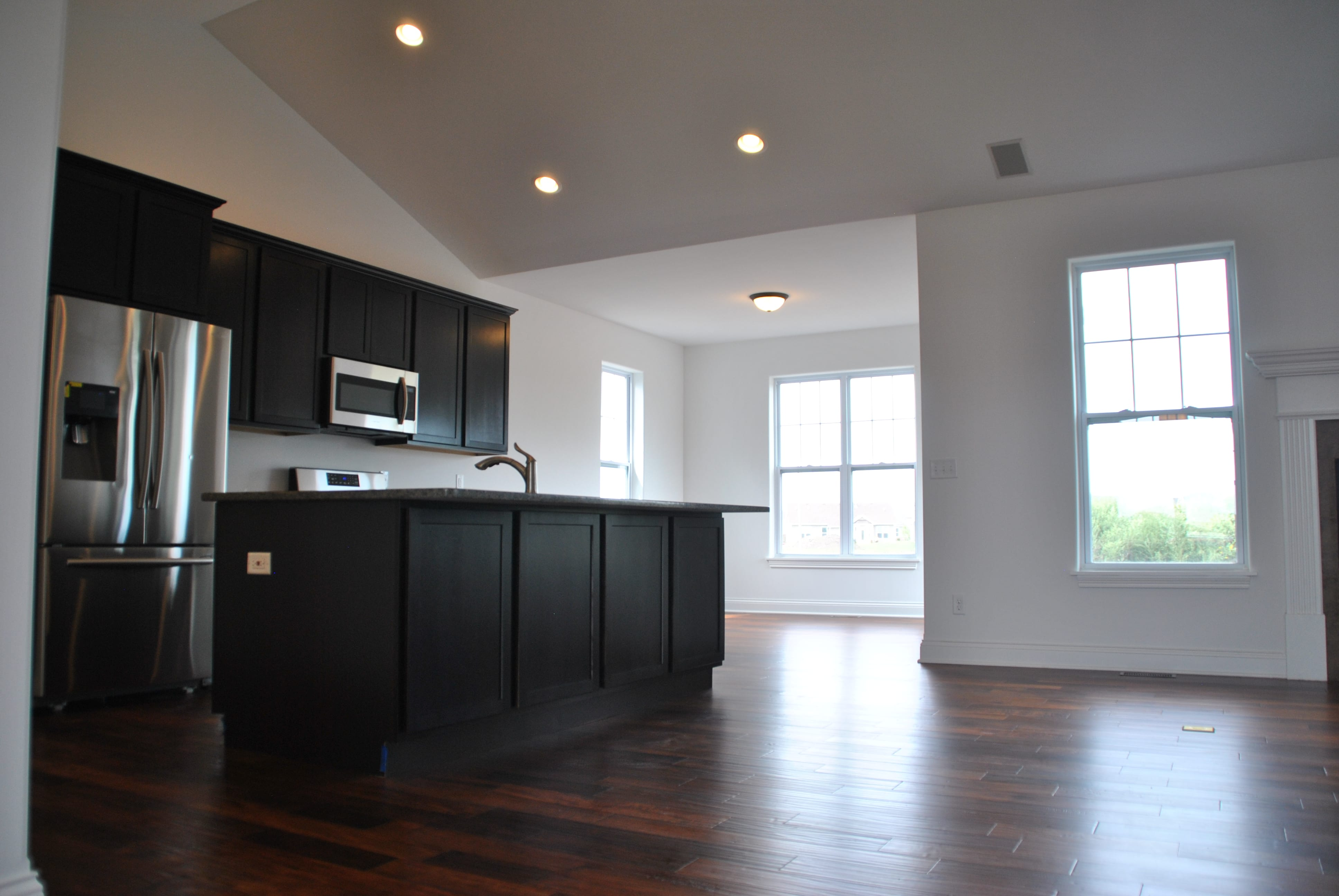 Kitchen with dark cabinets and acacia teak (dark colored) hardwood floor