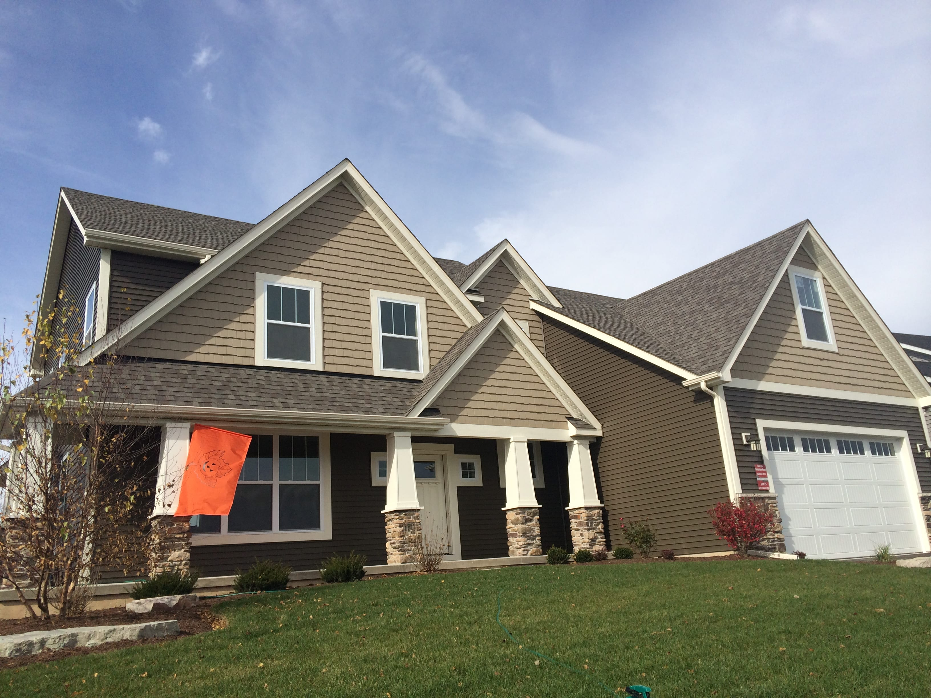 Exterior of a two story home with a pumpkin flag hanging from the front porch