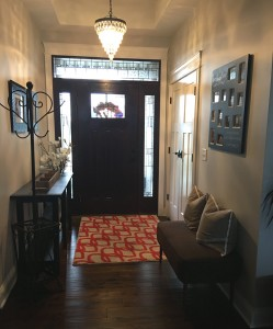 Foyer with orange rug and decor