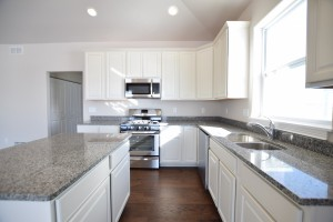 Kitchen with white cabinets and light granite