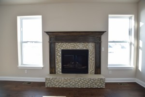 Fireplace with brown and cream tile, brown wood mantel