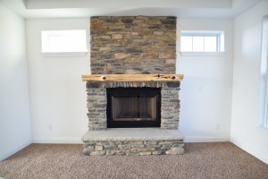 Fireplace with rustic wood mantel and brick floor to ceiling