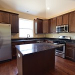 Kitchen with dark-stain cabinets and coordinating hardware