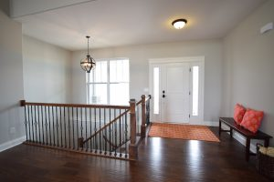 Staircase of ranch floorplan in entryway leading down to basement with classic iron rod design.