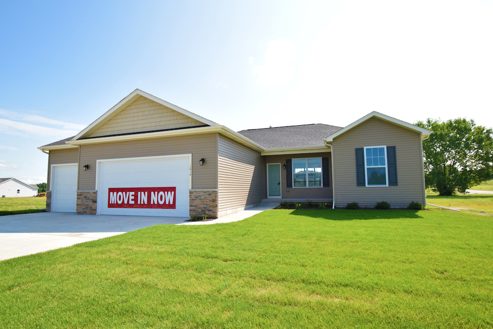 "Front exterior of a ranch style home with sign reading ""move in now"""