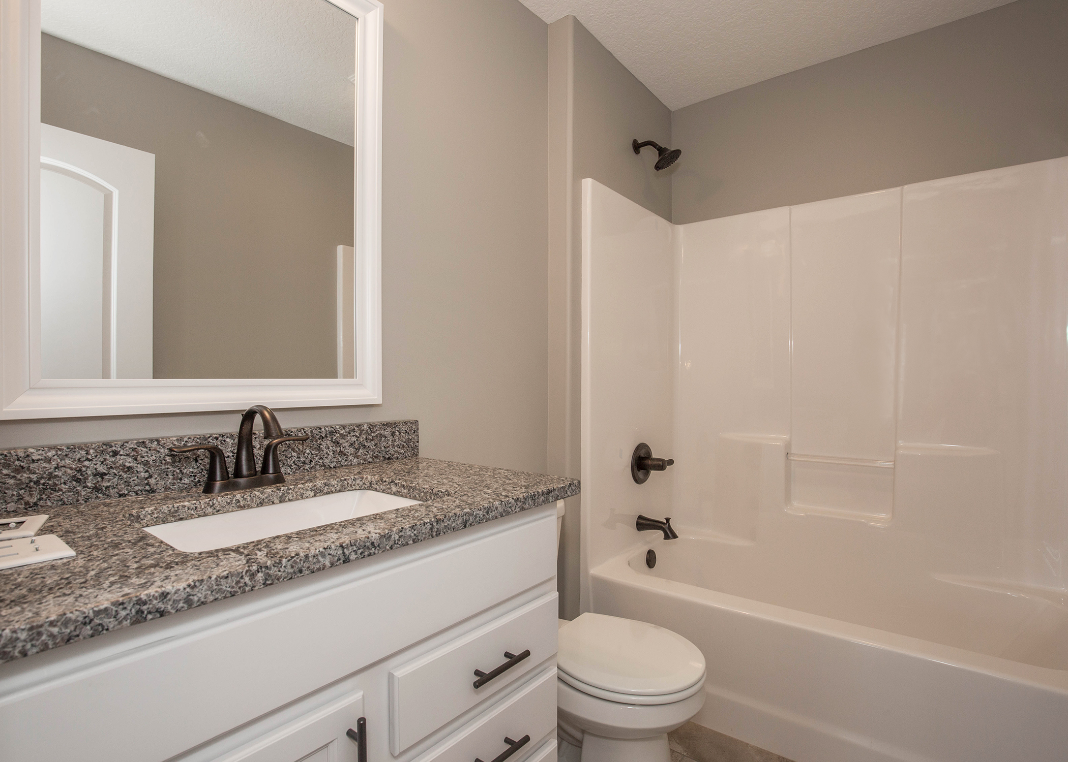Bathroom with shower and tub combination and single sink vanity