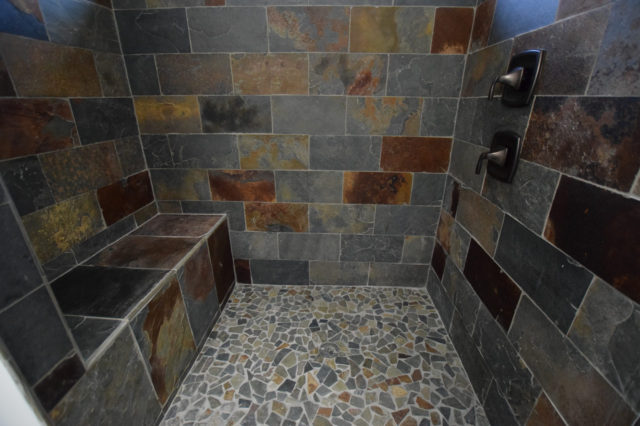 master bathroom shower with custom tile and bench